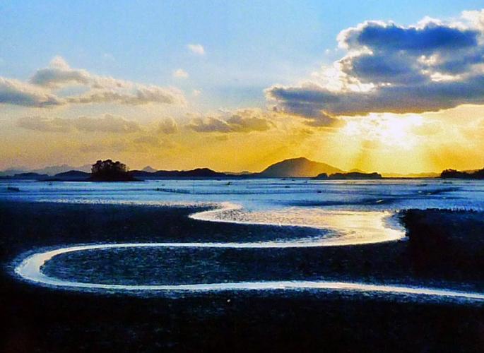 순천만의 일몰 모습. 쪽빛 하늘과 S자로 굽이쳐 흐르는 강하구. 그리고 석양을 가린 구름이 한폭의 그림과 같다. 순천만에서는 누구나 사진작가가 된다고 한다.