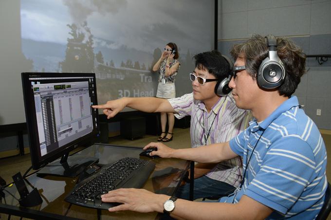 연구진들이 멀티채널 오디오 헤드폰 재생기술을 3D 영화를 보며 시연해 보이고 있다. 이 기술을 이용하면 영화나 TV 효과음을 22개로 구분해 현장감있는 소리를 들을 수 있다. - 한국전자통신연구원 제공