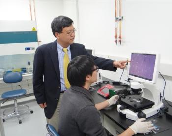 현미경으로 세포 조직을 살펴보며, 연구원과 토론하고 있는 명 단장. - 이충환 제공