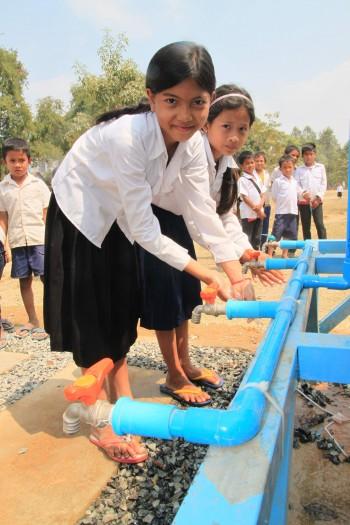 """'글로벌 물 적정기술센터'가 설치한 수돗가에서 손을 씻고 있는 본프놈초등학교 학생들. """"깨끗한 물을 마음껏 마실 수 있다""""며 즐거워했다. - 프놈펜=최영준 기자, jxabbey@donga.com 제공"""