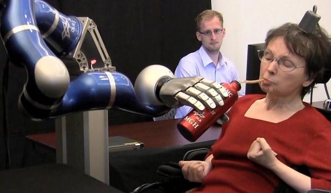 사지마비 환자가 생각만으로 로봇팔을 움직여 음료수를 마시는 모습. - 네이처 제공