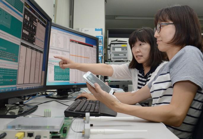 ETRI 연구진이 LTE-A 휴대전화를 무선 AP 크기의 스몰셀 기지국 하드웨어(HW)를 통하여 접속되는 과정을 시험하고 있다 - 한국전자통신연구원 제공