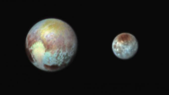 뉴호라이즌 탐사선이 최근접 하루 전인 13일 촬영한 명왕성과 위성인 카론의 모습. 가상의 색을 넣어 지형을 구별할 수 있게 했다. - 미국항공우주국(NASA) 제공