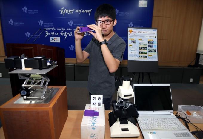 국무총리상을 수상한 박규열 군이 29일 자신의 발명품 '빔 스플리터를 이용한 이중반사식 현미경'을 설명하고 있다. 박 군은 값싸고 효율적인 개인 현미경을 구상하다 이 작품을 발명했다고 밝혔다. - 최혁중 기자 sajinman@donga.com 제공