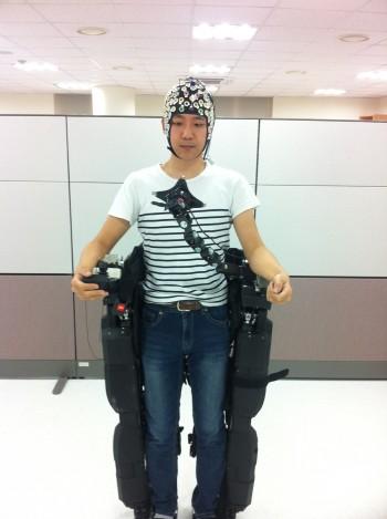 이성환 고려대 교수팀 소속 연구원이 뇌전도측정기를 착용하고 외골격 로봇에 올라탄 모습. 외골격 위에 부착된 LED 전구를 응시하면 뇌파를 해석한 신호를 받아 외골격이 움직인다. - 고려대 제공