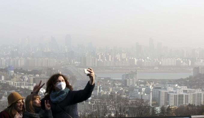 지난 봄 우리나라를 방문한 외국인이 황사로 뒤덮인 서울 시내 풍경을 배경삼아 기념사진을 찍고 있다. - 동아일보 제공