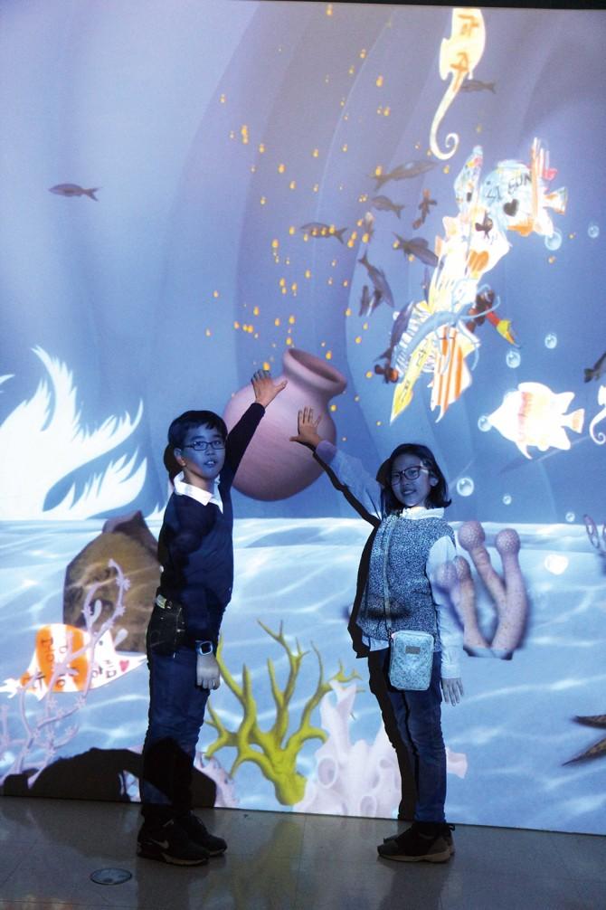 명예기자들이 스크린 속 물고기에게 먹이를 주고 있다. - 현수랑 기자 제공