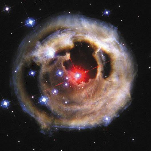 외뿔소자리의 V838(가운데 붉 은 별)과 그 주변 모습. V838은 2002년 1월 폭발적으로 밝아진 후 점차 어두워졌는데, 폭발에서 나온 빛이 주변의 먼지 덮개를 단 층 촬영하듯 연속적으로 비추고 있다. 2002년 10월의 모습이다. - NASA 제공