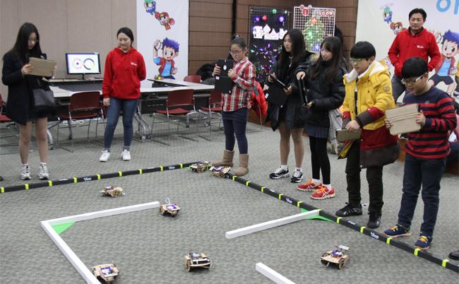 국립과천과학관에서 열리고 있는 아이루프 체험교실에서 학생들이 태블릿PC로 모형자동차를 구동시키고 있다. - (주)동아사이언스 제공