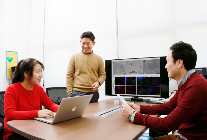 김정범 교수(가운데)와 이현아 연구원(왼쪽), 남동규 연구원(오른쪽)이 그래핀 지지체(모니터 그림)에 대해 이야기를 나누고 있다. - UNIST 제공