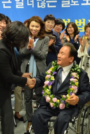 이상민 의원이 당선이 확실시 되자 지지자들로부터 화환을  받아 걸고 기뻐하고 있다. - 대전=전승민 기자 제공