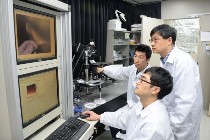 ETRI 최홍규, 최진식, 최춘기 연구원(좌로부터)이 측정장비를 이용해 그래핀 투명전극 필름의 특성을 확인하고 있는 모습 - 한국전자통신연구원 제공