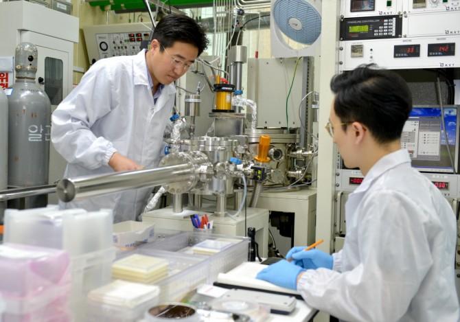 강상우 한국표준과학연구원 진공기술센터 책임연구원(왼쪽) 팀이 화학기상증착장비로 이차원 이황화몰리브덴을 큰 면적으로 합성하는 실험을 하고 있다. - 한국표준과학연구원 제공