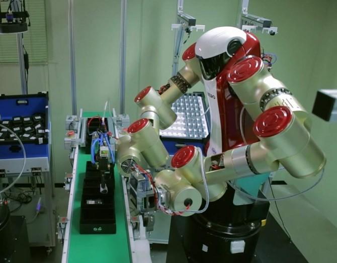 한국기계연구원과 로보스타가 공동으로 개발한 산업용 소형 양팔로봇 '아미로'가 휴대전화를 포장하고 있다. - 한국기계연구원 제공