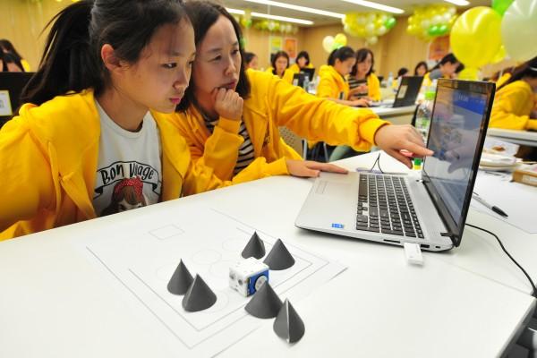 15일 서울 강남구 테헤란로 네이버 파트너스퀘어에서 열린 '맘앤걸스 코딩파티' 행사. 한 학생이 어머니와 나란히 앉아 소프트웨어를 제작해 로봇을 제어해 보고 있다. - 한국과학창의재단 제공