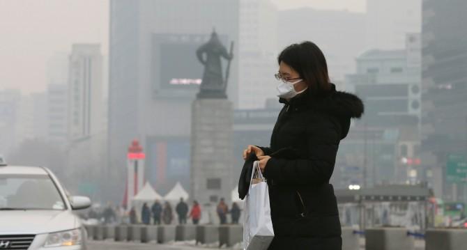 서울 도심 한복판을 가득 메운 미세먼지로 한 시민이 마스크를 끼고 길을 걷고 있다. 정부는 과학기술 기반 미세먼지 대응전략을 통해 2023년까지 사업장의 미세먼지 배출량을 절반으로 줄이기로 했다. - 유투브 캡처