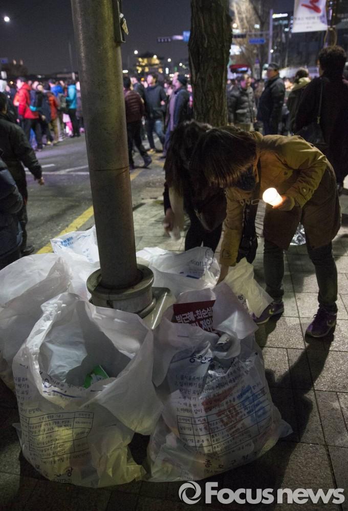 4일 오전 박근혜퇴진 6차 촛불집회에 참석한 시민들이 집회를 마무리하고 귀가길에 쓰레기를 임시로 마련한 봉투 속에 넣고 있다 - 포커스뉴스 제공