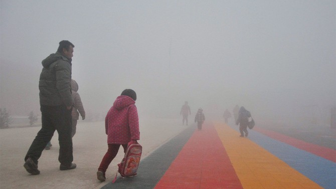 2015년 산둥 지역의 한 도로에서 중국인 아이와 부모가 뿌연 스모그를 뚫고 걷고 있다. 중국은 자유전자레이저(FEL)를발생시킬 수 있는 4세대 방사광가속기인 '다롄선형방사광가속기(DCLS)'를 이용해 스모그를 만드는 에어로졸 등 초미세먼지(PM2.5)의 생성과정을 규명할 계획이다. - 사이언스 제공