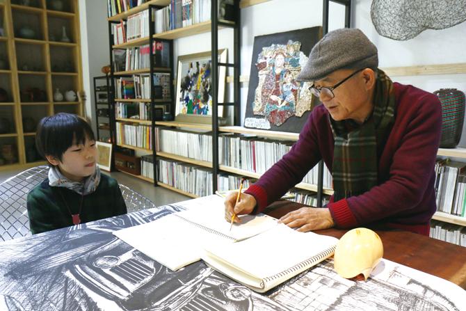 박종서 관장이 김대은 친구의 디자인 노트를 보며 이야기를 나누고 있다. - 김정 기자 제공