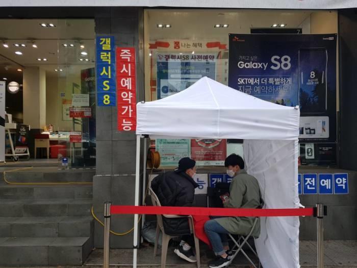 서울 종로구 SK텔레콤 T월드 카페 앞에서 두 명의 고객이 갤럭시S8 개통을 기다리고 있다. - 포커스뉴스 제공