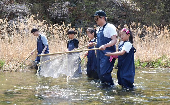가슴 장화를 입고 가족과 함께 족대로 민물고기를 잡는 탐사대원들. - 어린이과학동아 제공