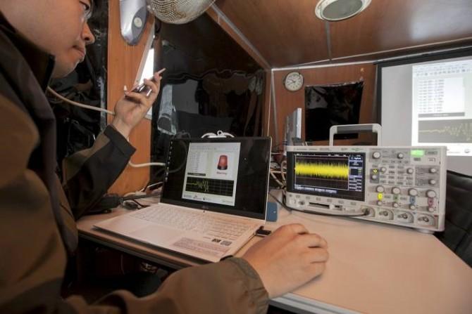 공동연구팀이 수중 통신으로 전달된 가상의 지진 경보를 특수 장비를 통해 확인하고 있다. - SK텔레콤 제공