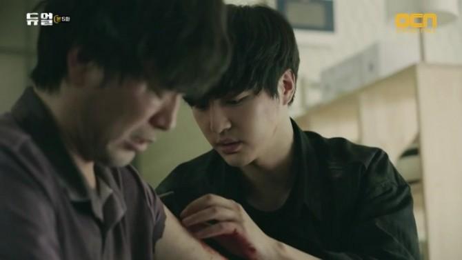 복제인간 1 이성준(오른쪽, 배우 양세종 분)이 능숙하게 찢어진 팔을 꿰메고 있다 - OCN 화면 캡처 제공