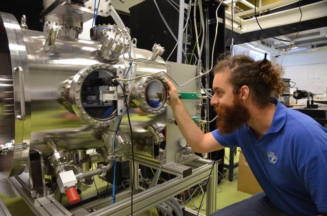 이스라엘 애서 연구소 연구원이 진공챔버 속에 설치한 초소형 인공위성 엔진의 동작 상태를 살펴보고 있다. - 전승민 기자 제공
