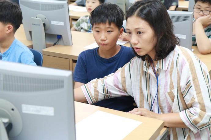 공주교육대에서 진행된 SW캠프에 참가한 학생이 엄마와 함께 컴퓨터 모니를 응시하며 코딩을 배우고 있다. - 커넥트재단 제공