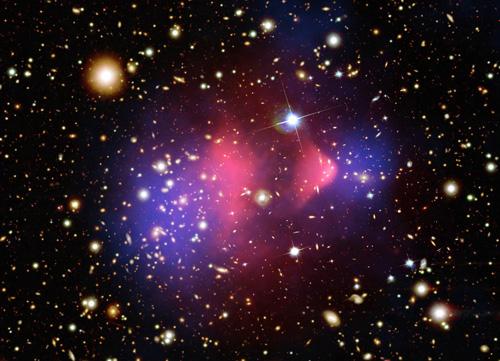 지구에서 빛의 속도로 37억 년 가야 하는 거리에서 두 개의 은하가 충돌했다. '총알은하단'이라고 불리는 이 천체를 X선으로 찍으면 가운데에 충돌한 은하가 모여 있지만(총알 모양), 중력만 따로 측정하면 좌우로 이미 지나간 모습(둥근 모양)으로 나온다. 보이지 않는 '암흑물질'이 존재한다는 간접증거다. - 미국항공우주국 제공