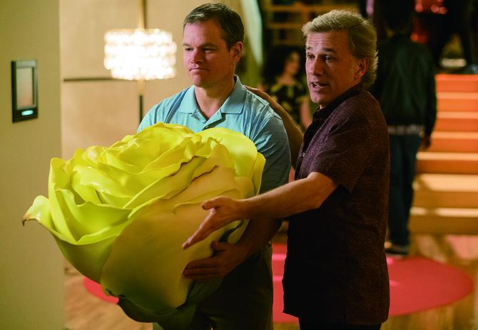 몸집만한 노란색 장미를 든 사프라넥. 소인국의 세상에는 현실세계의 물건을 판매하는 시장도 생겼다. -영화 '다운사이징'