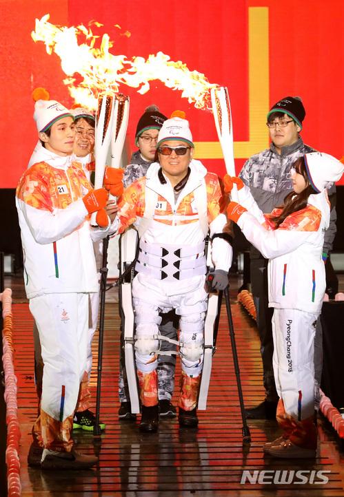 장애인 테니스 국가대표를 지낸 이용로(가운데)씨가 3일 평창 패럴림픽 성화 합화식에서 웨어러블 로봇을 착용하고 성화를 넘기고 있다.