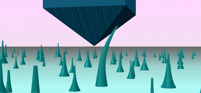 연구팀이 개발한 휘는 다이아몬드 바늘(아래 뾰족한 구조). 위에서 거대한 구조로 누르면 휘어진다. -사진 제공 MIT