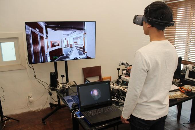 한 연구원이 가상현실(VR) 기기와 휴대용 뇌전도(EEG) 기기를 착용한 채 가상 공간을 거닐고 있다. 노트북 모니터에는 뇌파가 기록되고 있다. - 송경은 기자 kyungeun@donga.com