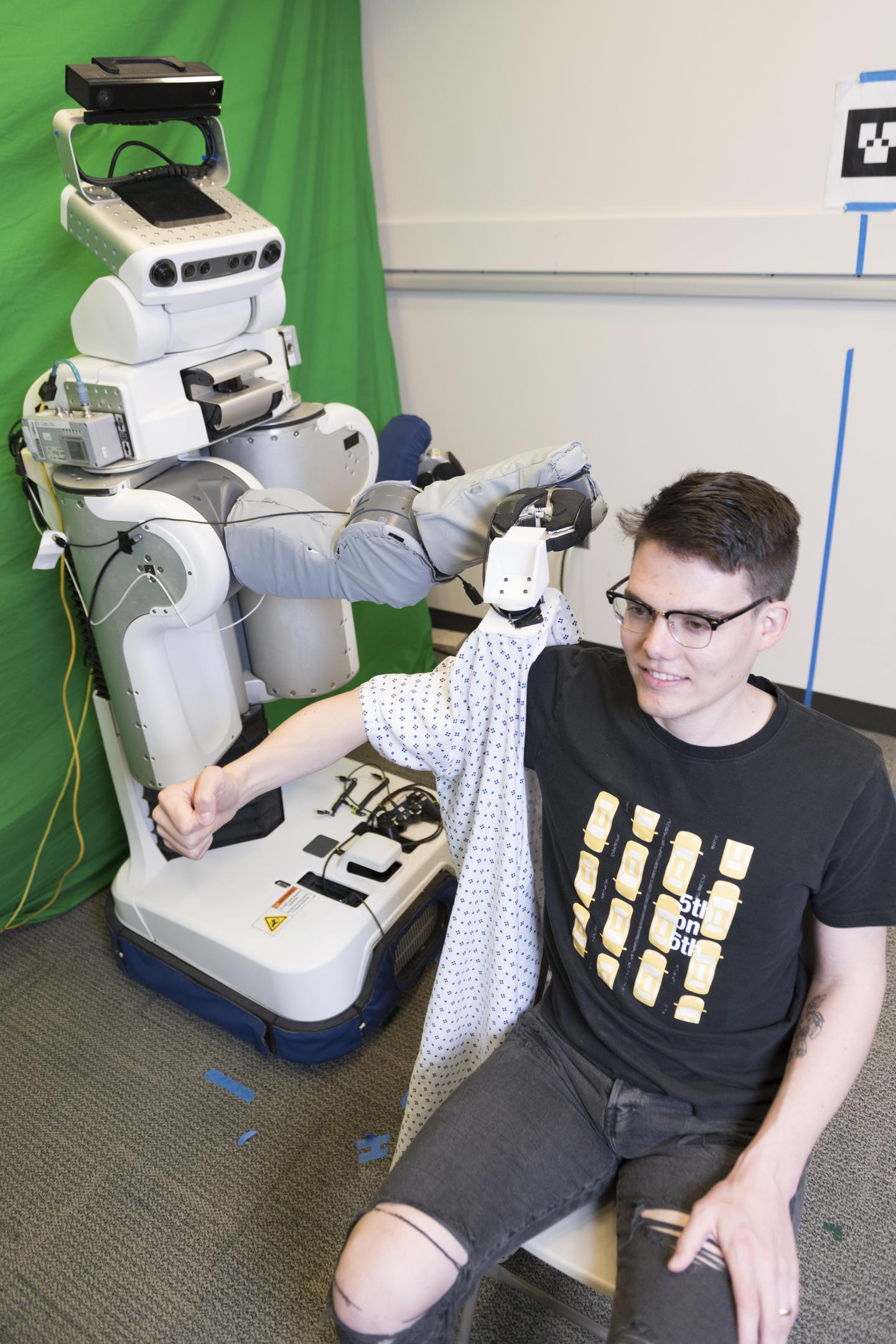 조지아공대 연구진이 개발한 로봇 PR2가 사람에게 가운 소매를 걸쳐주고 있다. - 조지아공대