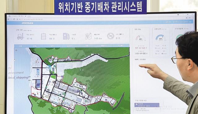두산중공업이 경남 창원공장에 최근 사물인터넷(IoT) 기술을 바탕으로 한 중장비 관리 시스템을 도입했다. 개발자인 윤석문 책임연구원이 지도 위에 표시된 중장비 정보를 가리키며 시스템에 대해 설명하고 있다. - 두산중공업 제공