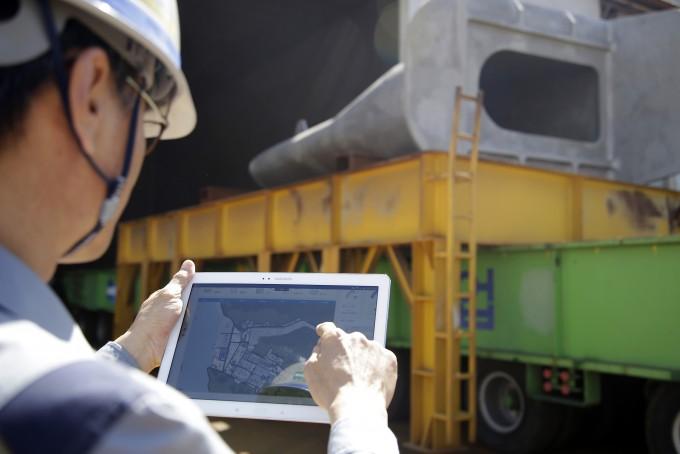 두산중공업 창원공장에서 관리자가 태블릿PC를 이용해 공장 내 중장비 작업 현황을 모니터링 하고 있다. 뒤로 보이는 것은 트랜스포터(운반장비)다. 창원공장 내 모든 중장비는 사물인터넷(IoT) 센서를 탑재하고 있어 실시간으로 작업과 관련된 다양한 정보가 중앙 서버로 전달된다. - 두산중공업 제공