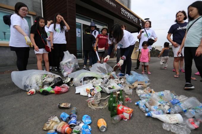 현장탐사에서 수거한 쓰레기를 분리수거하며 주로 어떤 종류의 쓰레기가 많은지 이야기하고 있는 모습.