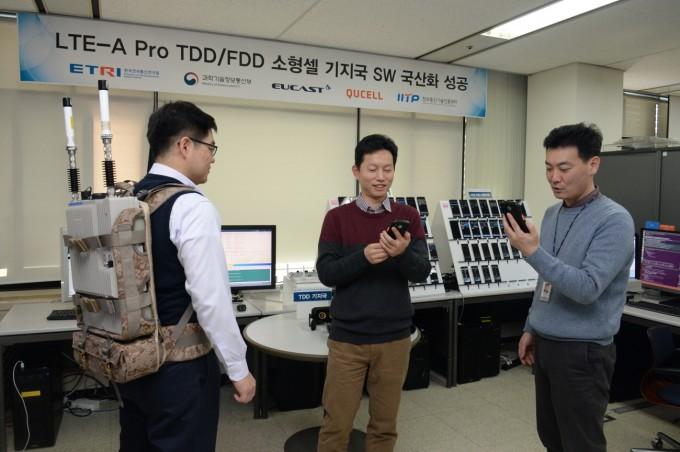 연구진이 지난 해 개발한 LTE-A 스몰셀 장비를 시연해 보이고 있다. 스몰셀 장비는 배낭형으로도 만들 수 있다.(왼쪽부터)유캐스트 김재형 대표, 전형준 연구소장, ETRI 김대익 책임연구원. 한국전자통신연구원 제공.