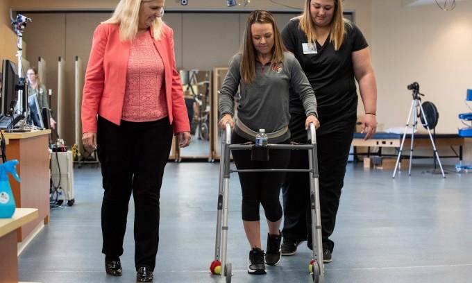 척수마비 환자인 켈리 토마스가 전기자극기와 보행 보조기를 이용해 걷고 있다. 루이스빌 대학.