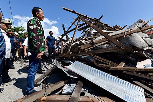 2018년 조코 위도도 인도네시아 대통령(앞)이 이틀 전 발생한 규모 7.5의 강진에 이은 지진해일(쓰나미)로 큰 피해를 입은 술라웨시섬 팔루를 찾아 무너져버린 건물 잔해를 굳은 표정으로 응시하고 있다. 1일 오후 현재 844명이 사망한 것으로 집계된 가운데, 수천 명이 숨졌을 가능성이 있다는 관측도 나오고 있다-동아일보 DB 제공