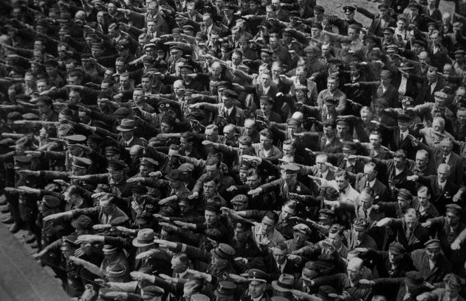 1936년 집회에서 나치식 경례를 하는 군중들. 군중 모두가 경례를 하고 있는데, 단 한 사람만이 시큰둥한 표정으로 팔짱을 끼고 있어서 화제가 된 사진이다(어디에 있는지 찾아보세요).- 위키미디어