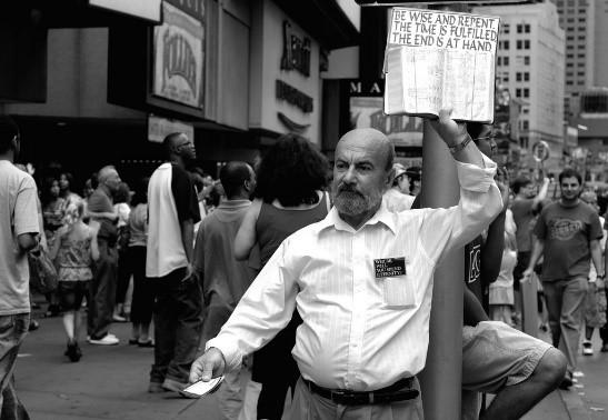뉴욕 타임스퀘어에서 '종말이 가까웠다'는 피켓을 들고 있는 남자. 대도시의 번화가에는 늘 세상의 멸망과 위험을 경고하는 '이상한' 사람이 있지만, 오류 관리 이론에 의하면 이런 터무니없는 묵시론적 예언이 사실은 '적응적 행동'일 가능성이 있다.- 플리커 제공