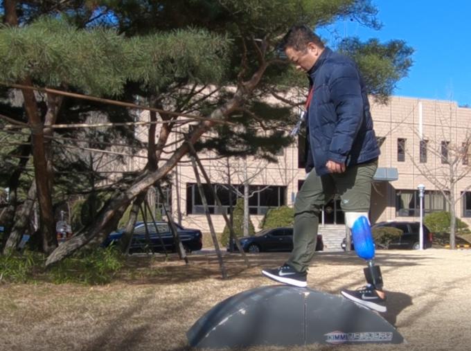 4년 전 교통사고로 왼쪽 다리를 잃은 교사 김진곤 씨(49)가 한국기계연구원이 개발한 스마트 로봇의족을 착용하고 언덕을 오르고 있다. 수동의족은 발목이 90도 각도로 고정돼 있는 반면 로봇의족은 노면 등 주변 상황에 맞게 자동으로 발목이 움직여 자연스럽게 언덕이나 계단 등을 오르내릴 수 있다. - 과천=송경은 기자 kyungeun@donga.com