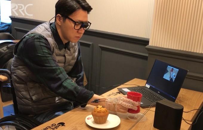인간중심소프트로봇기술연구센터(SRRC) 연구진이 개발한 인공지능(AI) '비디오넷(VIDEO-Net)'을 활용한 지능형 웨어러블 로봇 손을 착용한 손 마비 환자가 커피 잔을 스스로 들고 있는 모습. 비디오넷은 안경에 달린 카메라로 내려다 본 영상(노트북의 화면)에 나타난 사용자의 팔 움직임과 물체와 손의 상대적 위치와 상호작용 등을 토대로 사용자 의도를 파악하고 웨어러블 로봇 손에 다음 동작을 명령한다. - SRRC 제공