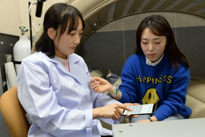 김아영 ETRI 연구원(오른쪽)이 자체 개발한 생체신호 복합센서로 생체신호를 측정하고 있다. -사진 제공 ETRI