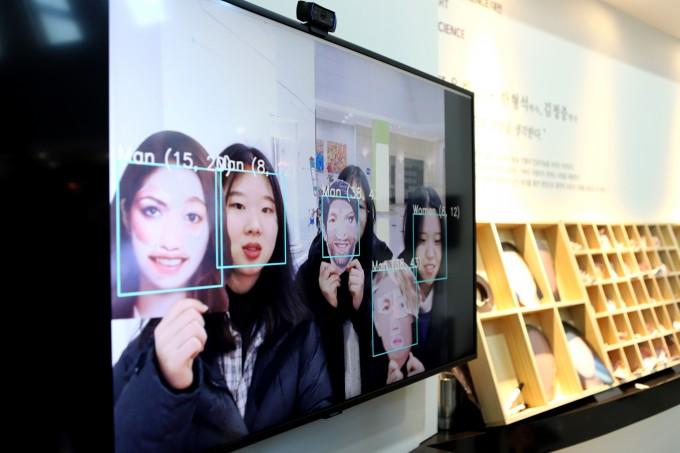 사람들이 '실존과 비실존의 경계 1'에서 AI를 대상으로 직접 그린 얼굴과 진짜 사람 얼굴을 속이는 체험하고 있다. AI가 유추한 성별과 나이가 화면에 보인다