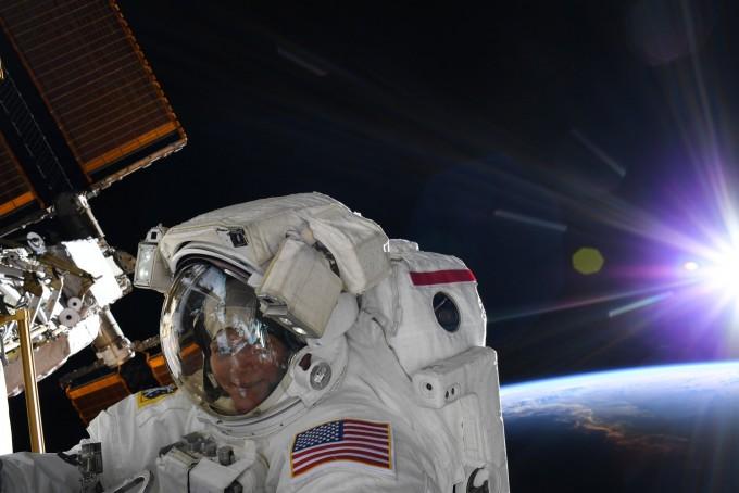 22일 우주 유영에 나섰던 앤 매클레인의 모습 너머로 지구가 보인다. 앤 매클레인 트위터
