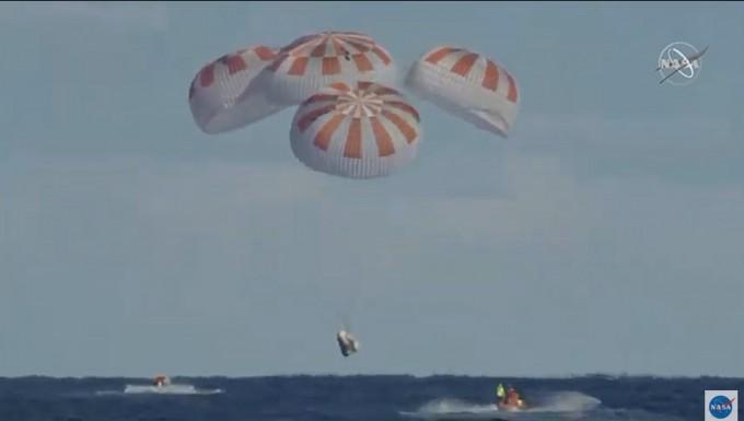 최초의 민간우주유인선 크루드래건의 시험선이 8일 밤(한국시간) 무사히 지구에 돌아왔다. 사진은 착륙 직전 낙하산을 펼치고 내려오다 착륙하기 직전의 모습이다.. NASA TV 캡쳐