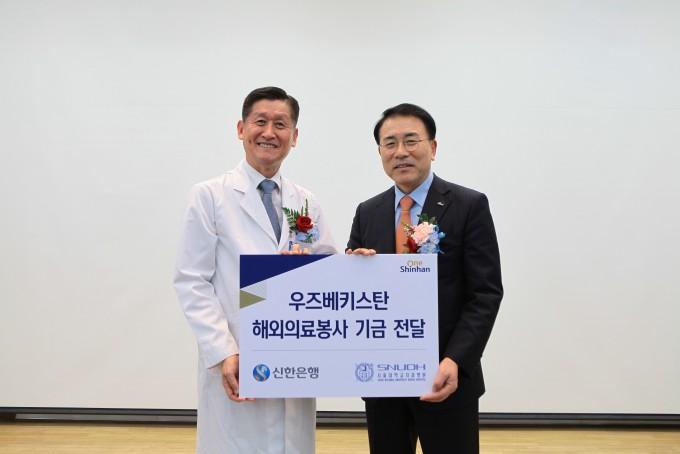 신한금융그룹 조용병 회장(오른쪽)이 서울대치과병원 허성주 병원장(왼쪽)에게 우즈베키스탄 해외의료봉사 기금을 전달하고 있다